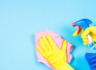 Woman cleaning blue wall with microfiber rag and cleaning spray.